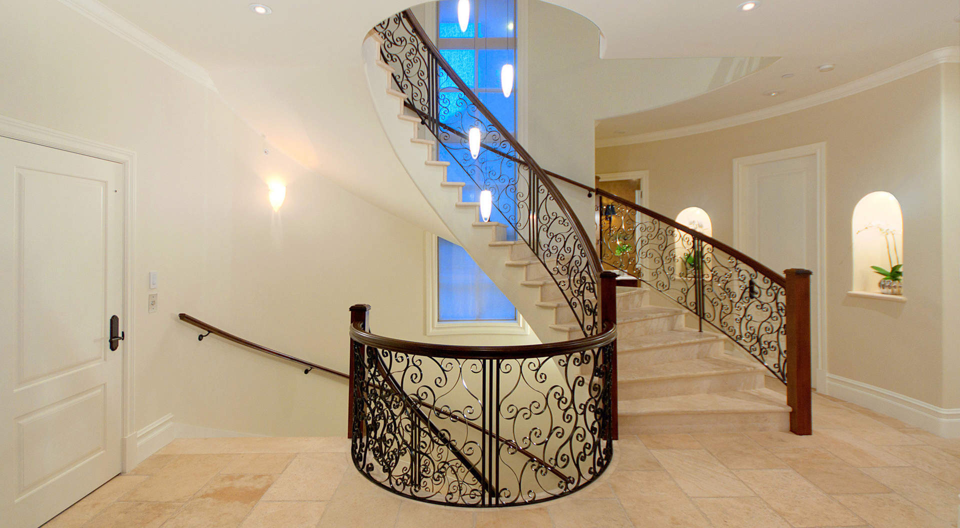 Curved Staircase with Solid Marble Treads & Custom Wrought Iron Railing